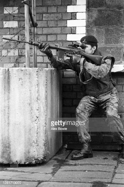 A British army marksman provides cover for his squad as the foot patrol passes between concrete security bollards sited on the interface dividing...
