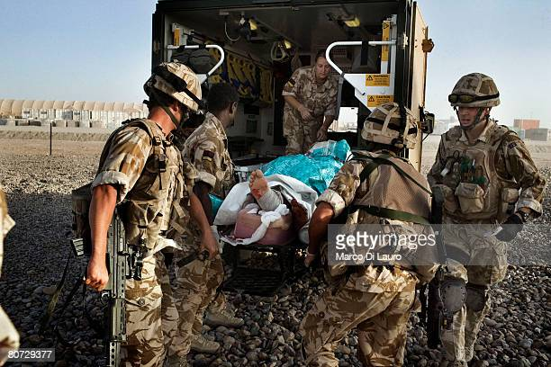 British Army Medical Emergency Response team from the UK Med Group carry injured Afghan National Army Sgt. Quem Abdulh into an ambulance, on June 11...