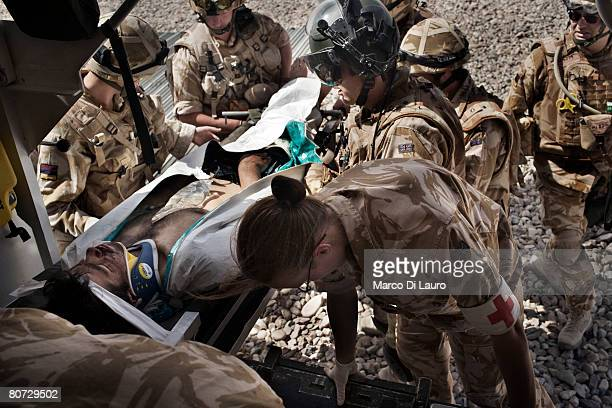 British Army Medical Emergency Response team from the UK Med Group load Afghan National Army soldier Bashir into an ambulance as he is brought in by...