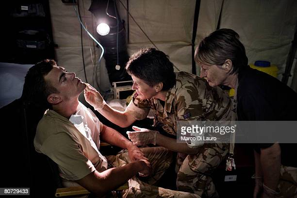 British Army nurses Capt Lindsay Baigent and Captain Anne Stavelyon clean a British soldier's face wound from a non combat incident before stitching...