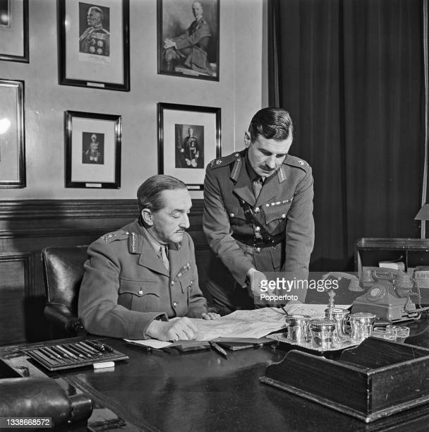 British Army officer General Sir Alan Brooke , Chief of the Imperial General Staff , seated at a desk studying a map with, on right, Archibald Nye ,...