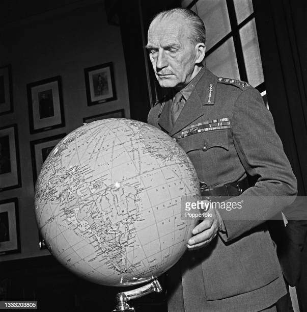 British Army officer General Sir John Greer Dill , Chief of the Imperial General Staff, studies a globe in his office in London during World War II...
