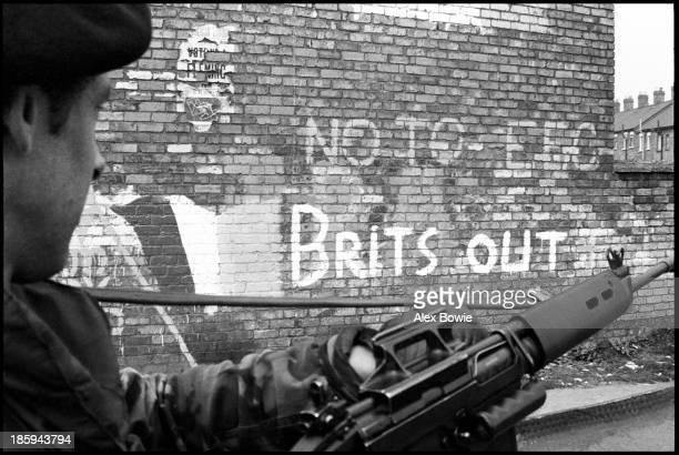 British Army patrol moves past IRA graffiti in the Republican Ardoyne district of north Belfast 19th April 1976