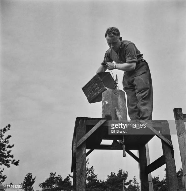 A British Army recruit fills a portable field shower at a military training camp somewhere in England 1942 Original Publication Picture Post 1095...