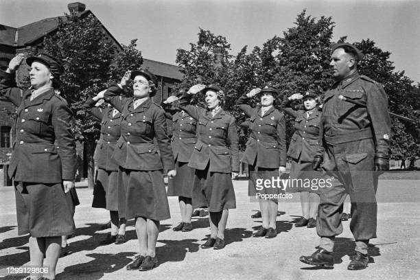 British Army Regimental sergeant major looks on as women recruits from the Auxiliary Territorial Service salute on a parade ground at Lichfield in...