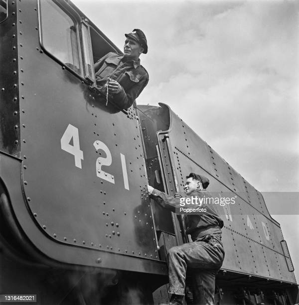 British Army seconded engine driver and fireman climb in to the cab of their War Department Stanier Class 8F locomotive number 421 to await the right...