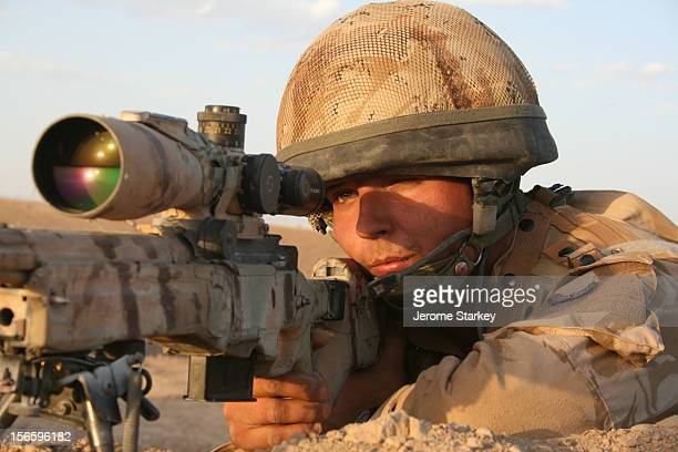 British army sniper peers through the scope of his rifle to scan the horizon for suspected Taliban insurgents north of Musa Qala in Helmand...