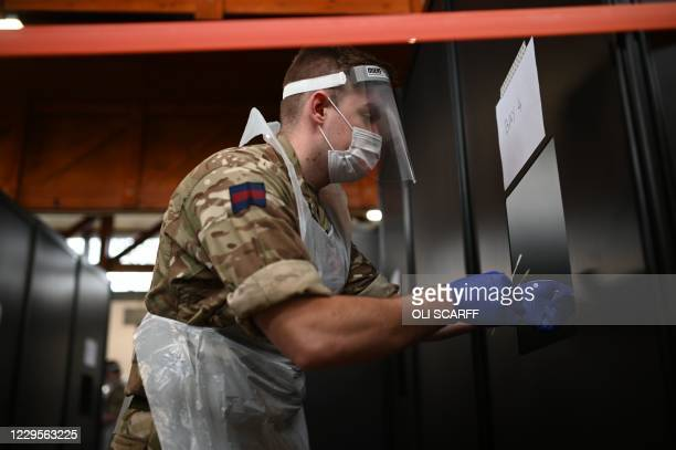 British Army soldier, 1st battalion Coldstream Guards, receives completed tests at a coronavirus testing centre set up at the Merseyside Caribbean...