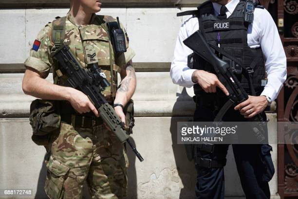 A British army soldier and a police officer secure an entrance to the British Foreign and Commonwealth Office in central London on May 25 after...