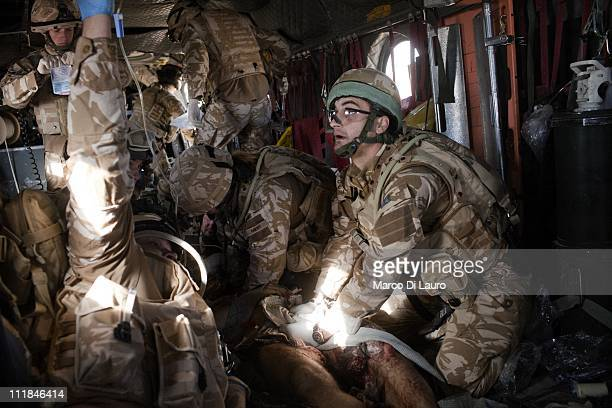 British Army soldier FLT LT Nick Welsh 38yearsold member of the IRT onboard of the MERT CH47 Chinook helicopter applies direct pressure on the wounds...
