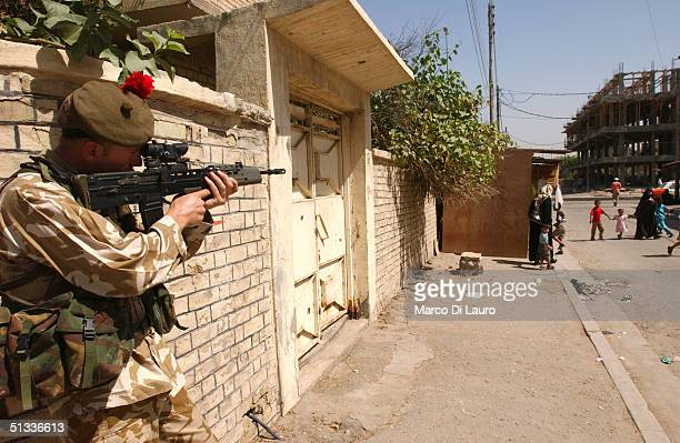 British army soldier from the 1st Black Watch Regiment aims his rifle to secure the street while on foot patrol September 22, 2004 in Basrah which is...