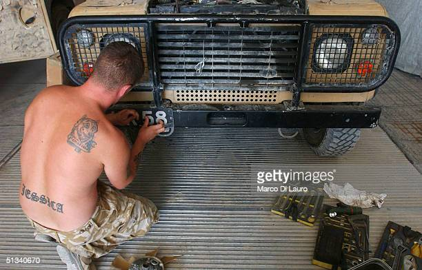 British army soldier from the 1st Cheshire Regiment works on his armored Land Rover Defender at his base at the Shat Al Arab Hotel September 23 2004...