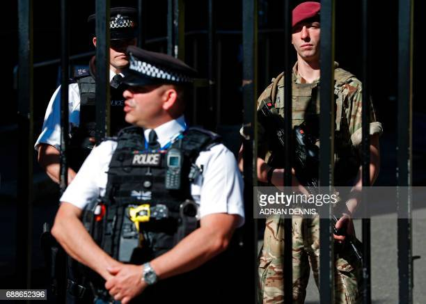 A British army soldier from the Parachute Regiment stands alongside a police officer behind the gates to Downing Street the official residence of...