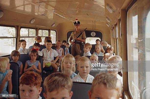 A British Army soldier from the Royal Regiment of Fusiliers guards expatriate school children on a bus in Aden during the Aden Emergency a period of...