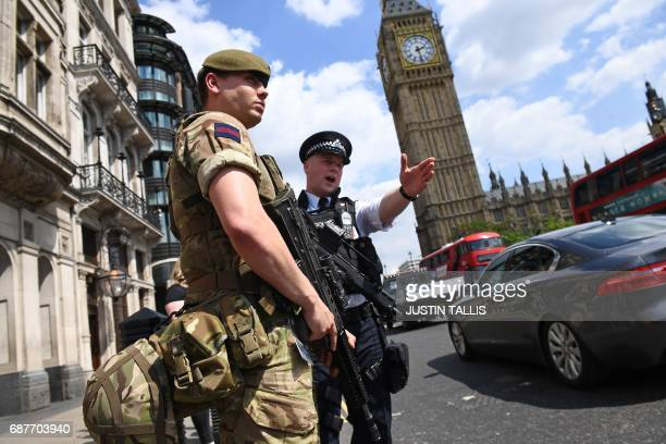 British Army soldier patrols with an armed police officer near the Houses of Parliament in central London on May 24 2017 Britain deployed soldiers to...