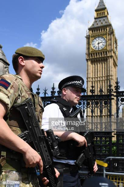 A British Army soldier patrols with an armed police officer near the Houses of Parliament in central London on May 24 2017 Britain deployed soldiers...