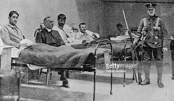 British army soldier stands guard over Irish republican prisoners in a temporary hospital at Dublin Castle following the Easter Rising, Ireland,...