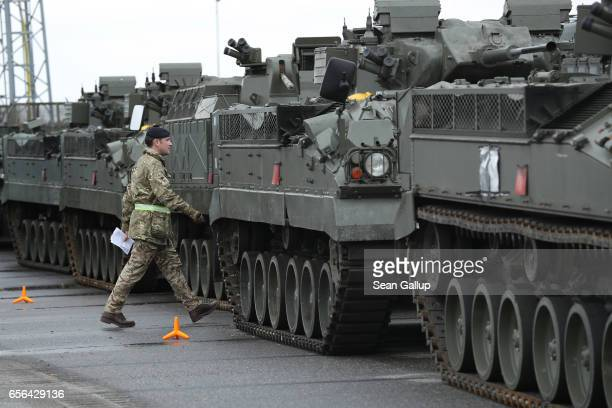 British Army soldier walks past Warrior tanks of the 5th Battalion The Rifles after the tanks and other heavy vehicles arrived by ship on March 22...