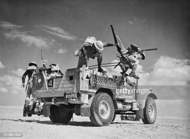 British Army soldiers from Middle East Command jump from their Morris CS8 15 Cwt truck to take up their positions in a training exercise in the...