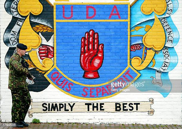 British army soldiers patrol the Lower Shankill area in front of a mural by the Ulster Defense Association the largest Protestant paramilitary group...