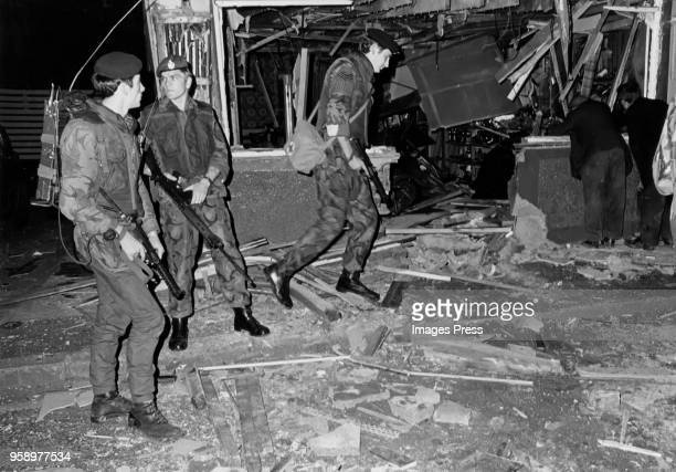 British Army soldiers walk by a destroyed storefront in the Falls Road area in Belfast, Ireland.