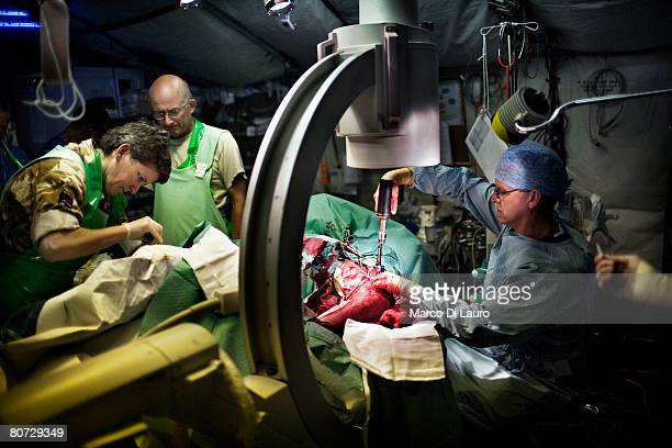 British Army surgeon Major Andy Bruce drills into a bone to place an external fixation to hold together the fracture on Afghan National Army soldier...