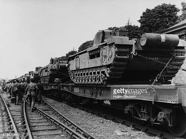 British Army tank crews make their way across a London Midland and Scottish Railway siding to a train carrying Churchill tanks on route to an unknown...