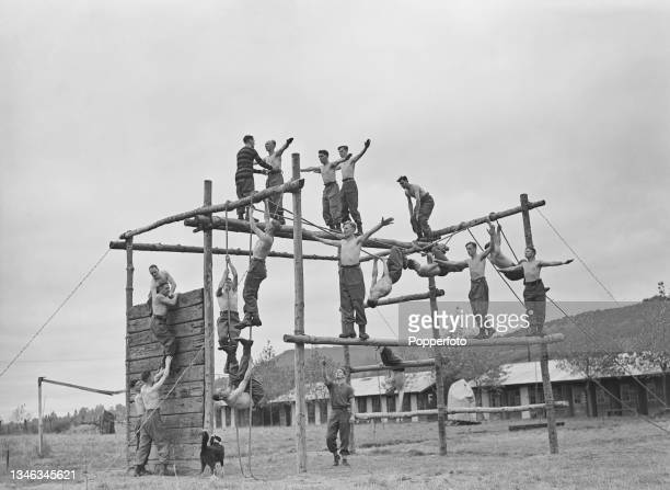 British Army trainee PT instructors climb on and over a monkey cage as part of a physical fitness routine at a Royal Army Physical Training Corps...