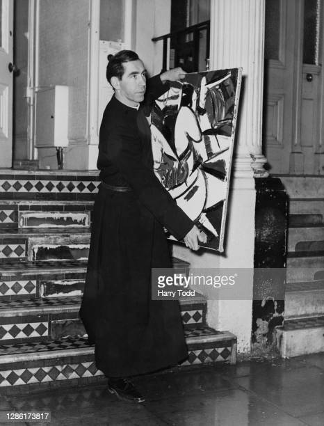 British artist and clergyman John Pelling carrying one of his paintings out of his home in Cheniston Gardens in Kensington, London, England, 16th...