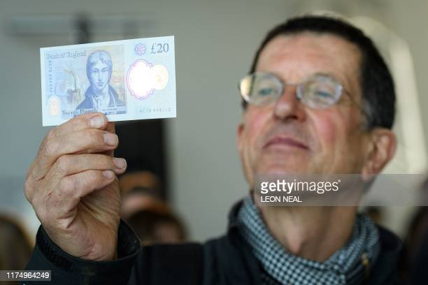 British artist Antony Gormley looks at the detail on a sample of the new twenty pound note featuring late British painter JMW Turner, during the...