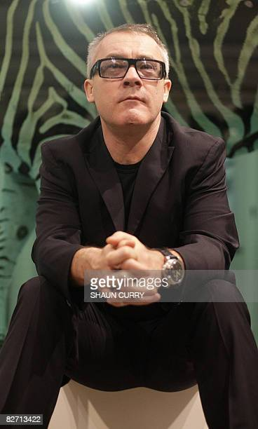 British artist Damien Hirst poses for photographs in front of his work entitled 'The Incredible Jouney' during a photocall at Sotheby's art gallery...