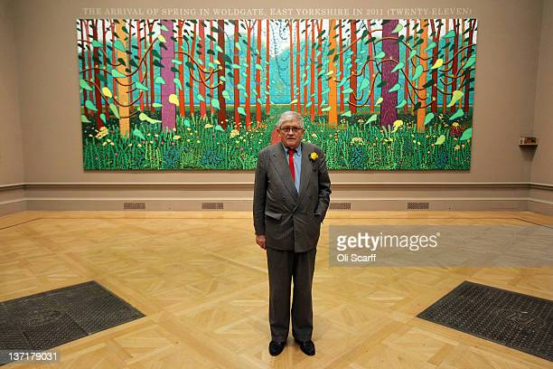 """British artist David Hockney poses in front of his painting entitled """"The Arrival of Spring in Woldgate, East Yorkshire in 2011 """" at the opening of..."""