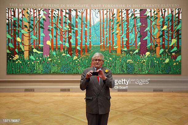 British artist David Hockney takes a picture of press photographers with his mobile phone as he poses in front of his painting entitled 'The Arrival...