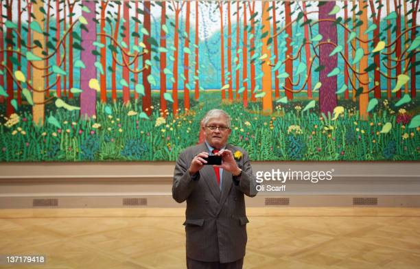 """British artist David Hockney takes a picture of press photographers with his mobile phone as he poses in front of his painting entitled """"The Arrival..."""