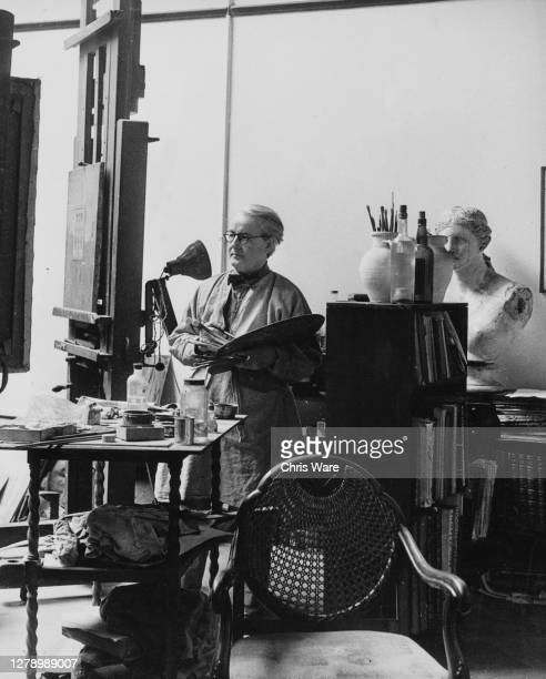 British artist Harold Workman holding a palette and wearing a smock as he stands behind an easel beside a freestanding shelving unit with artists'...