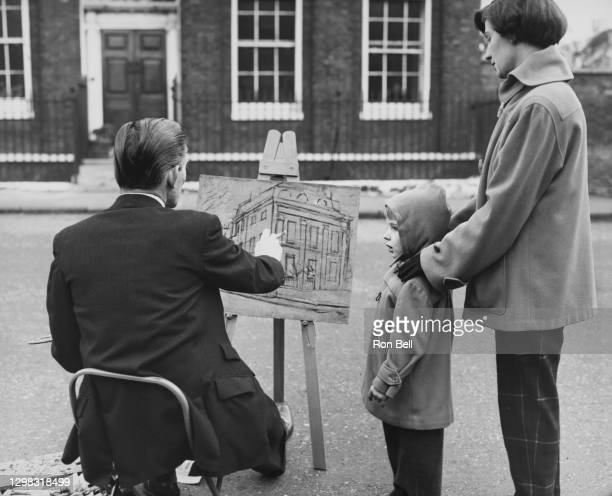 British artist James Neal watched by his wife Doreen and son Jonathan, as he sits at his easel as he works on a painting of a property in Canonbury...