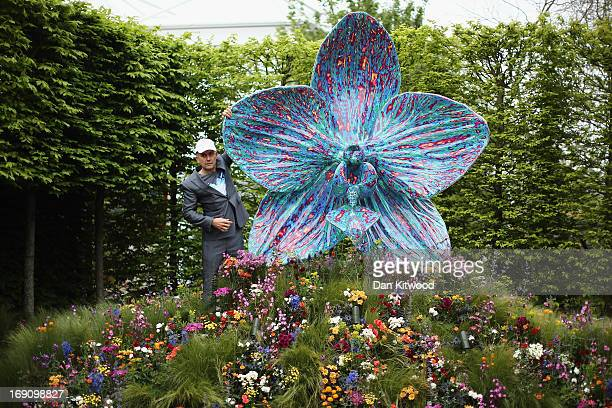 British artist Marc Quinn poses with his sculpture of an orchid in the Royal Horticultural Society garden during the Chelsea Flower Show press day on...