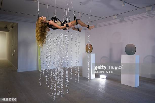 British artist Millie Brown performs Rainbow Body a performance installation where she is surrounded by crystal prisms suspended from the ceiling at...