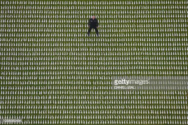 British artist Rob Heard poses for a photograph amongst 72396 shrouded figures which form his installation Shrouds of the Somme laid out at the Queen...