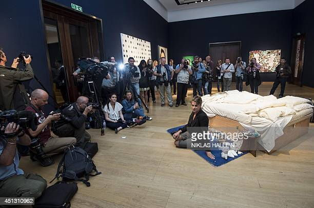 British artist Tracey Emin sits on her iconic art installation My Bed during a press preview at Christie's auction house on June 27 2014 Tracey...