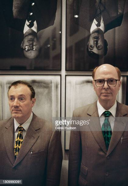 British artists duo Gilbert and George pose for pictures under a photo collage of themselves upside down exhibited in the Paris art museum, the...