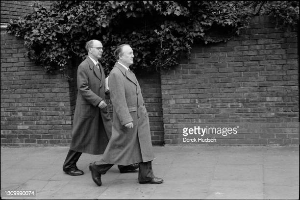 British artists Gilbert and George pose on the street with an unknown passer by.