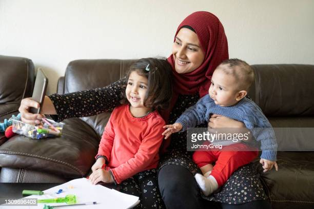 british asian mother and children taking selfie at home - religious dress stock pictures, royalty-free photos & images