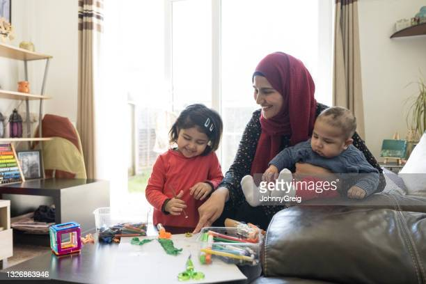 british asian woman with baby and daughter during craft time - baby stock pictures, royalty-free photos & images