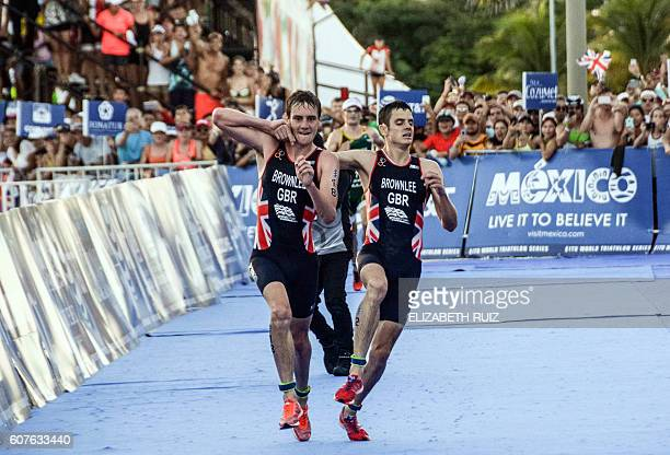 TOPSHOT British athlete Alistair Brownlee helps his brother Jonathan Brownlee before crossing the line in second and third place during the ITU World...