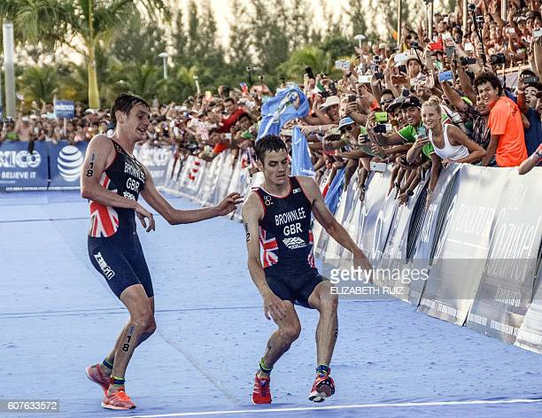 British athlete Alistair Brownlee helps his brother Jonathan Brownlee before crossing the line in second and third place during the ITU World...
