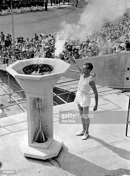 British athlete bears the Olympic Torch into the Empire Stadium at Wembley London and inaugurates the 1948 Olympic Games by lighting the ceremonial...