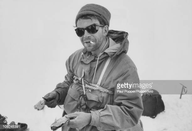 British athlete Chris Brasher uses his penknife to cut up a dried salted fish during a storm on the Ushba Plateau of the Caucasus Mountains Georgia...