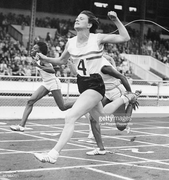 British athlete Dorothy Hyman crosses the finish line to win the 100 yard sprint during a US verses UK track and field meet at White City Stadium...