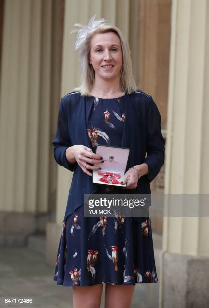 British athlete Georgina Hermitage poses with her medal after she was appointed a Member of the Order of the British Empire at an investiture...